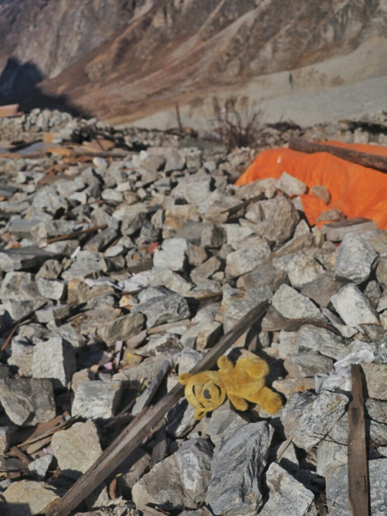 A lonely teddy bear laying around in the rubels where Langtang Village once used to be