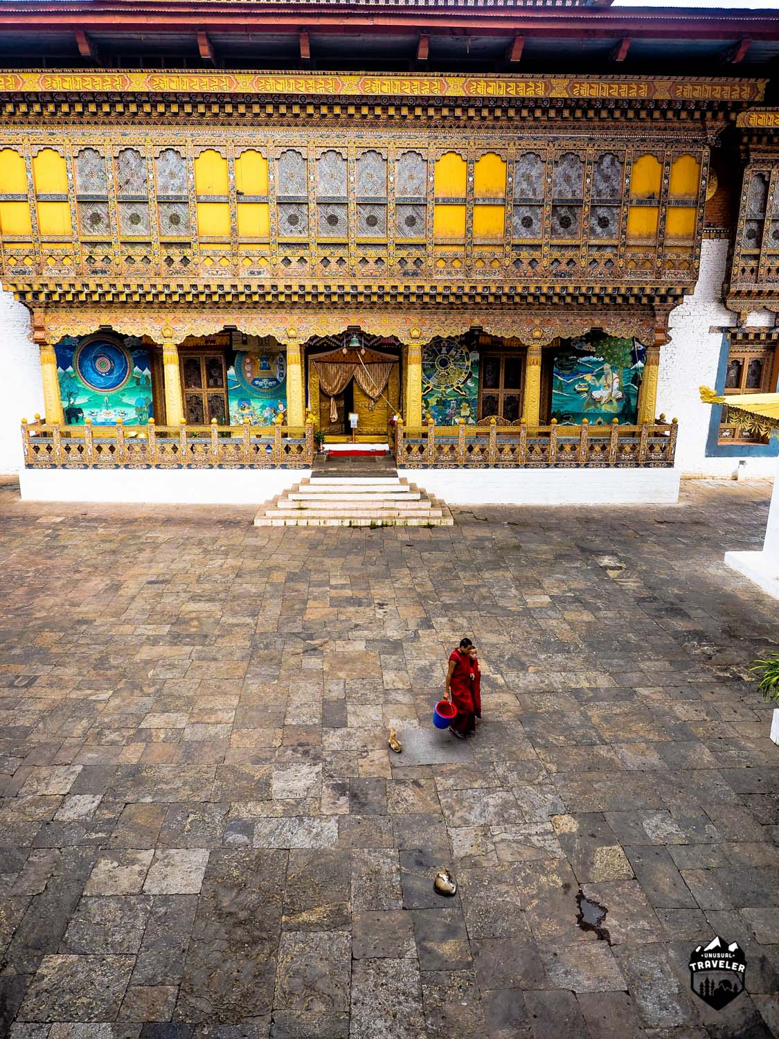 Two monks walking across the main square inside Punakha Dzong
