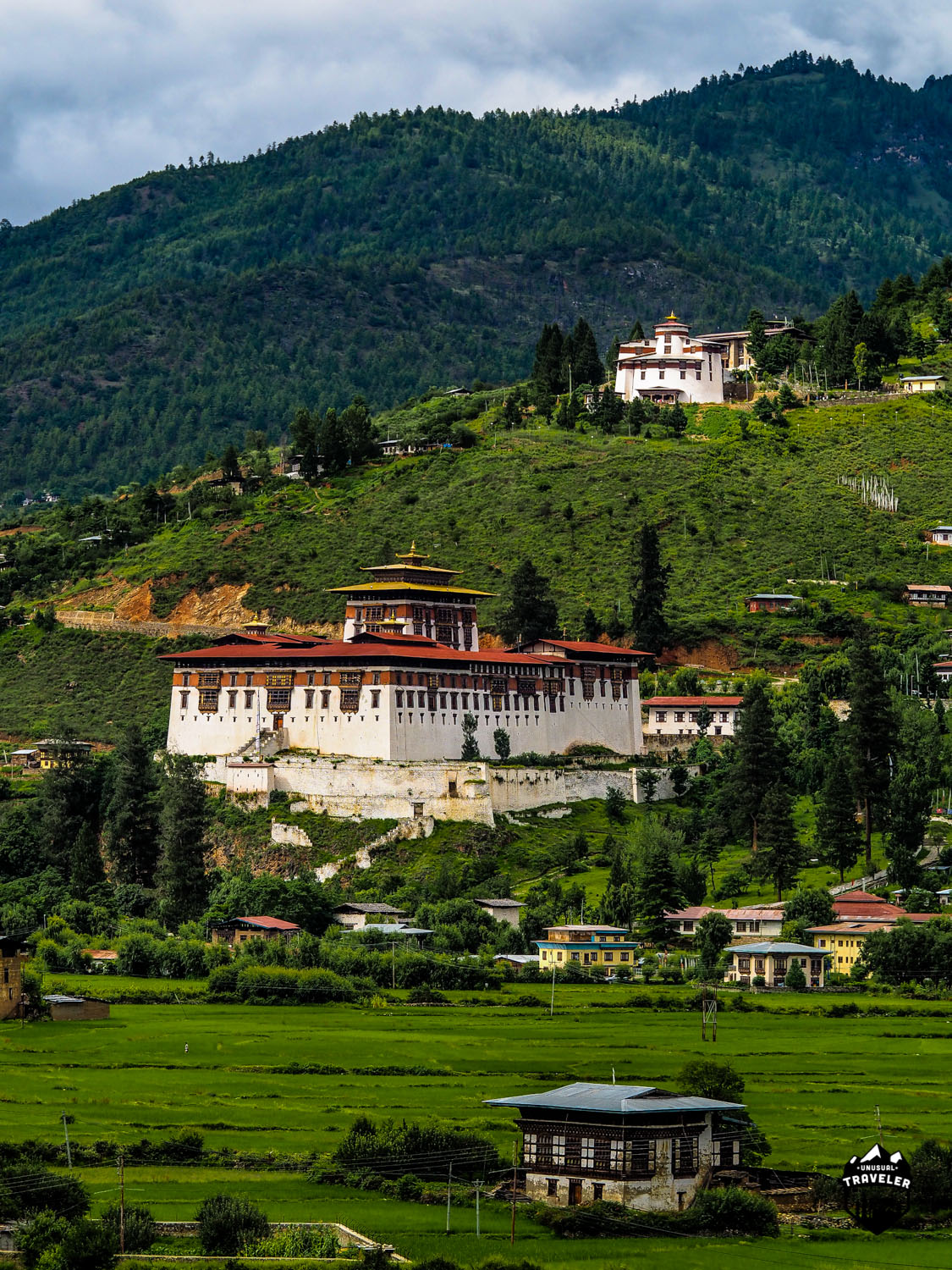 Paro Dzong and Bhutan National Museum in Paro Valley. Even the big city's is surrendered by nature and paddy fields.
