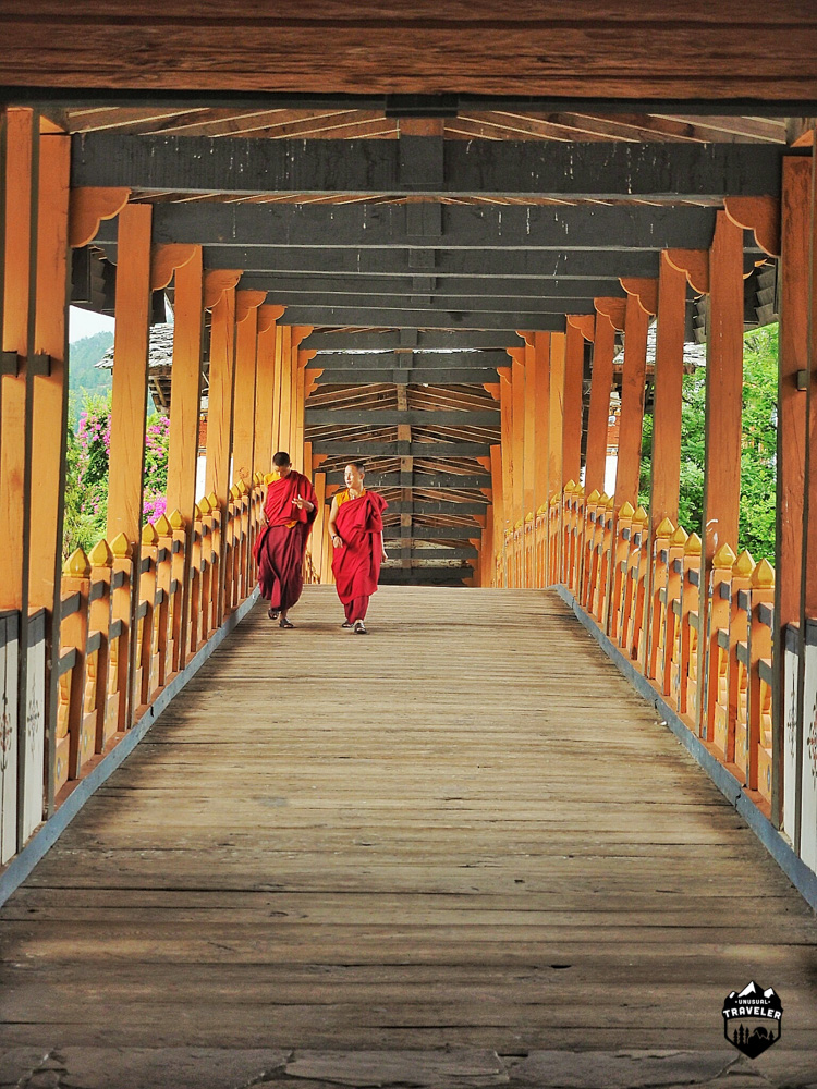 Two monks walks across the bridge that leads to the Dzong.
