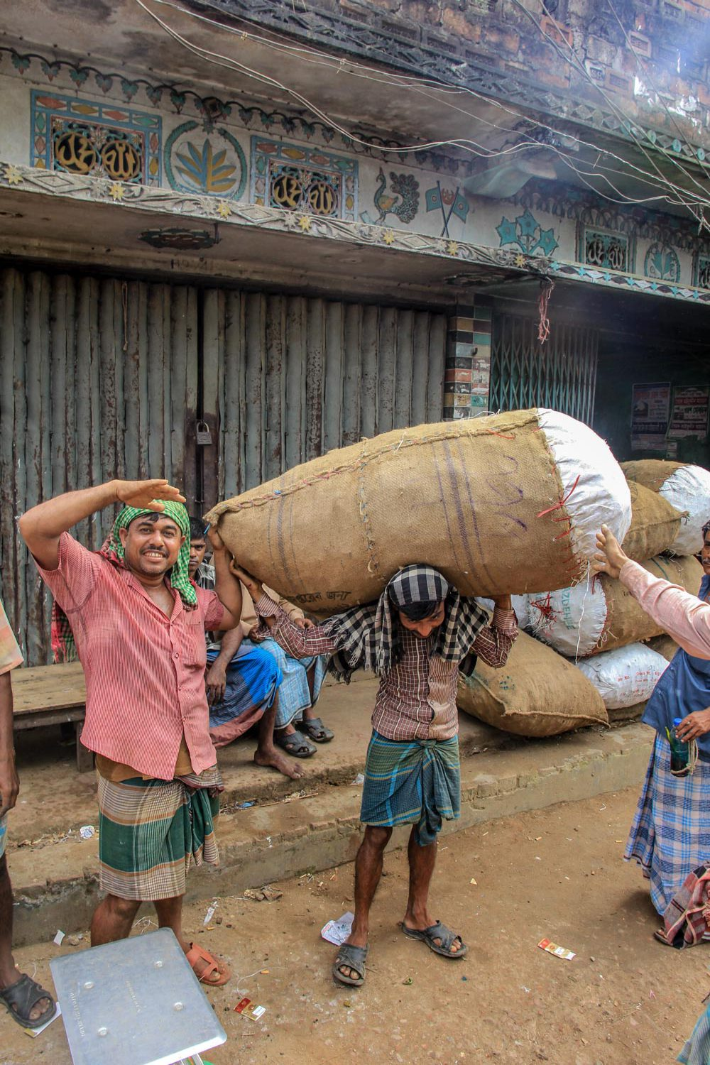 Local posing for a photo, the person on the left side told his friend to lift the heavy bag just for the photo in Bangladesh