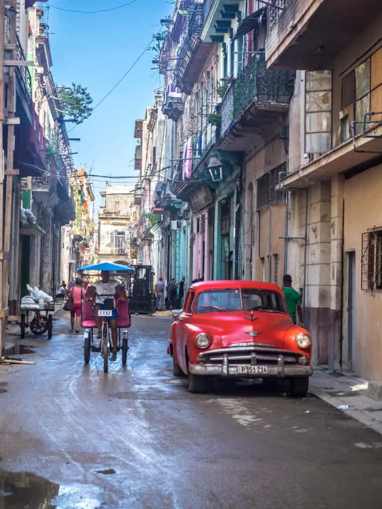 A back street with a red car and man riding a back in Havana, Cuba