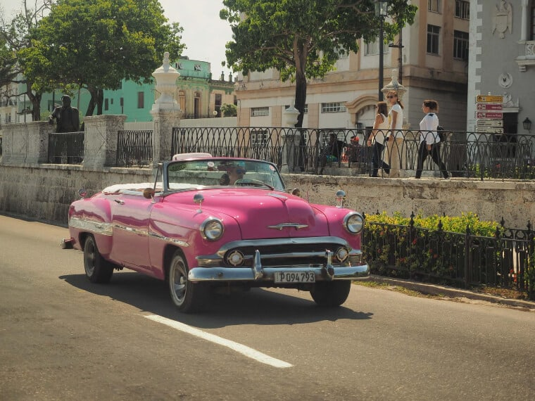 A pink car driving through the streets of Cuba