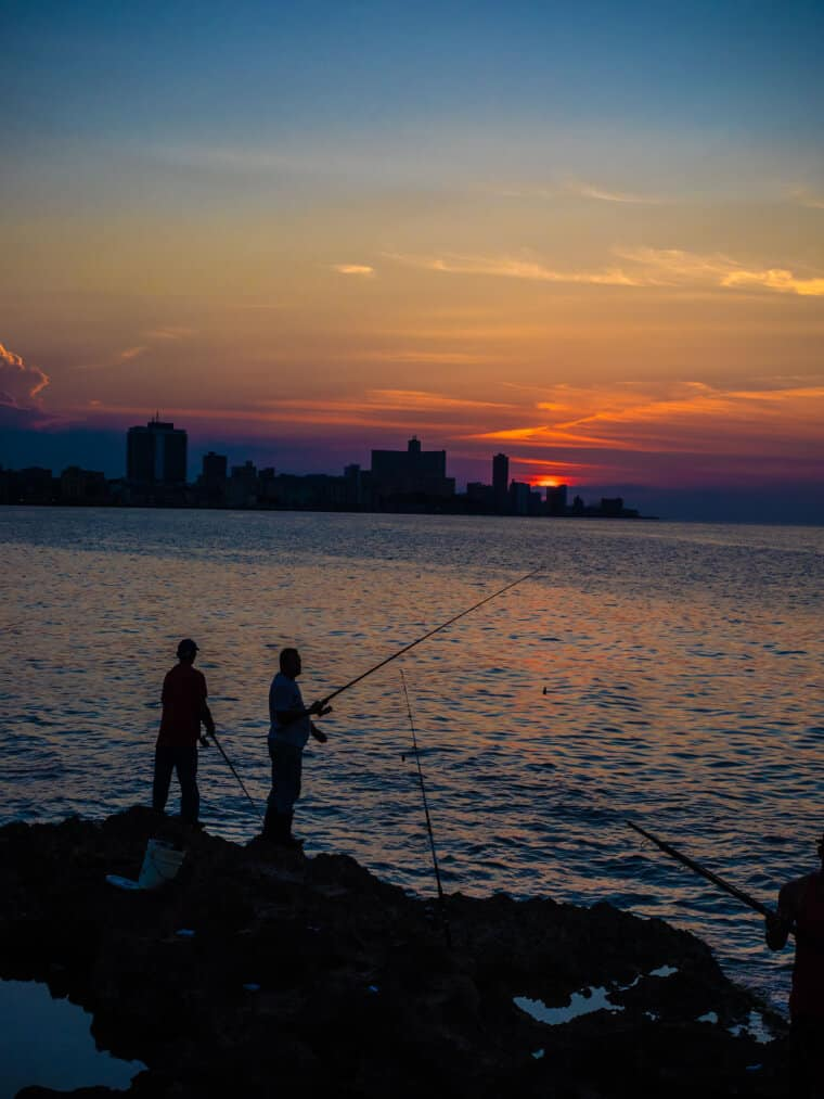 Two people fishing from the rocks at sunset