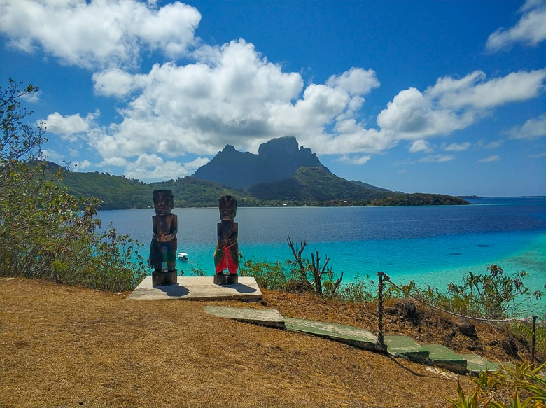 Two Tiki statues overlooking the lagoon and Mata Pupu and Mt Otemanu in Bora Bora