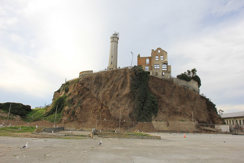 Alcatraz Island Lighthouse, with the burned-out Social Hall travel guide